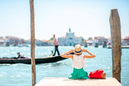 桟橋の上に座って、ヴェネツィアに浮かぶゴンドラとヴェネツィアの運河の美しい景色を楽しむ若い女性の旅行者