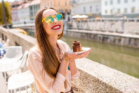 Young woman enjoying traditional slovenian chocolate cake near the river in the center of Ljubljana city. Traveling Slovenia