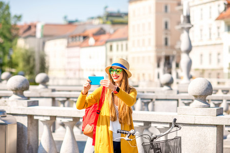 Young female traveler photographing city with smart phone standing with bicycle on Triple bridge in Ljubljana. Traveling in Slovenia Stock Photo