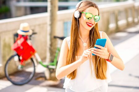 Young smiling woman listening to the music with headphones and smart phone standing on the street with bicycle on the background at the sunny weather