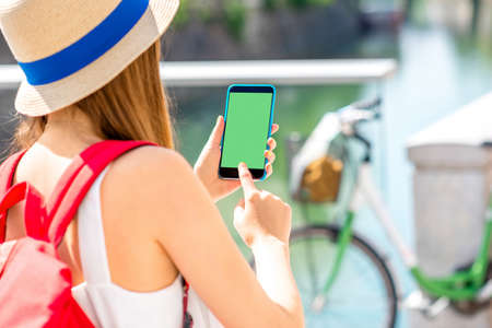 green screen: Female traveler holding smart phone with green screen on the street with bicycle on the background.