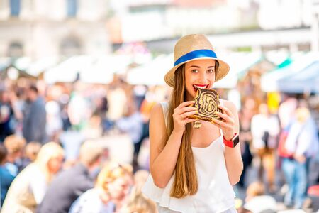 holiday food: Young woman tasting traditional slovenian dessert Potica at the open market square in Ljubljana. Slovenian street food. Image with small depth of field and composition with copy space