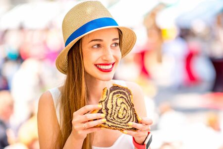 Young woman tasting traditional slovenian dessert Potica at the open market square in Ljubljana. Slovenian street food. Close up view with small depth of field. Stock Photo
