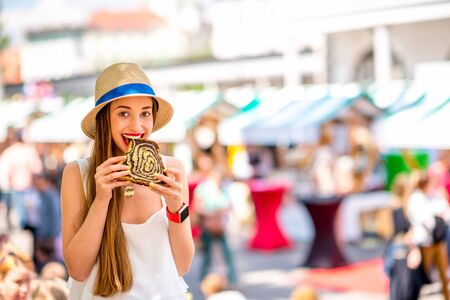 Young woman tasting traditional slovenian dessert Potica at the open market square in Ljubljana. Slovenian street food. Image with small depth of field and composition with copy space