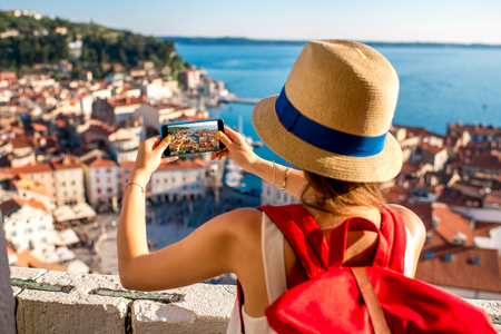 Young female traveler with red backpack and photo camera enjoying the view on Piran old town. Traveling in Slovenia Stock Photo - 60999207