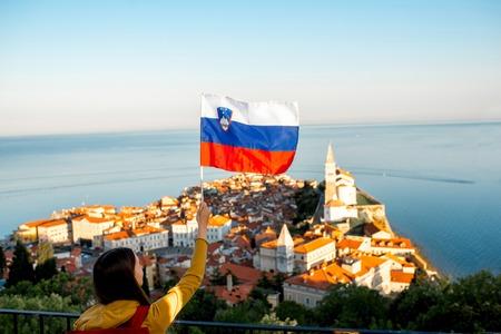Jonge vrouw zwaaien Sloveense vlag op Piran kustplaats achtergrond. Bevordering van het toerisme in Slovenië
