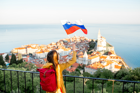 Young woman waving slovenian flag on Piran coastal town background. Promoting tourism in Slovenia