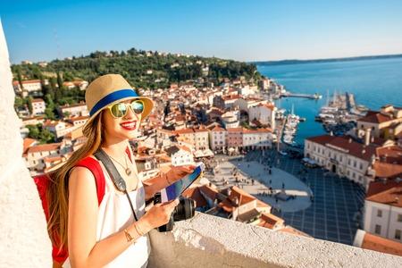 Jonge vrouwelijke reiziger met rode rugzak en hoed genieten van het uitzicht vanaf de toren George's op Piran oude stad. Reizen in Slovenië