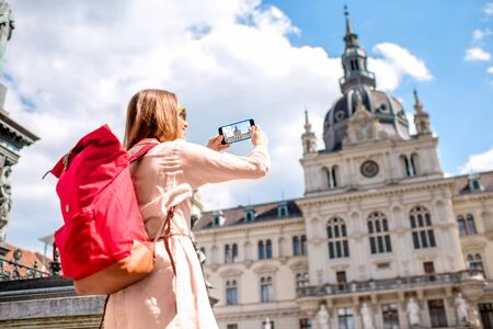 hauptplatz: Young woman photographing with phone town hall building in Graz old town. Traveling in Austria