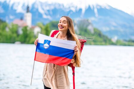 promoting: Young female tourist with slovenian flag standing near Bled lake, popular tourist destination in Slovenia. Promoting tourism in Slovenia Stock Photo