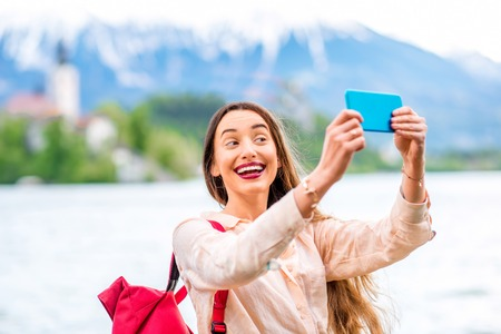 Young female tourist making selfie portrait with Bled lake and mountains on the background. Tourist having fun traveling in Slovenia