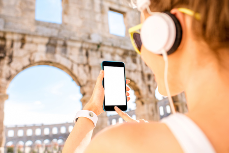 Young sports woman in headphones holding smartphone with white screen on the ancient amphitheatre background Stock Photo
