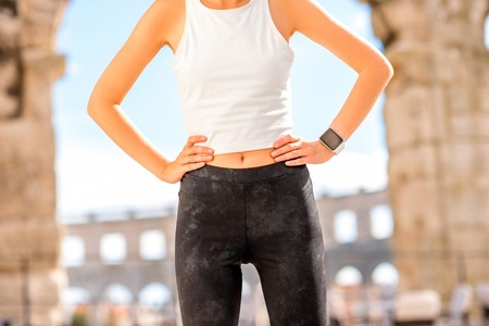 amphitheatre: Beautiful waist of sports woman in white t-shirt and black leggings outdoors near the old roman amphitheatre Stock Photo
