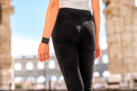 Beautiful sports woman legs in black leggings outdoors near the old roman amphitheatre