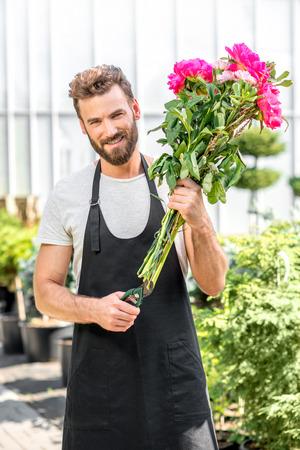 J - 2 60995221-fleur-beau-vendeur-faisant-un-beau-bouquet-de-pivoines-roses-dans-le-magasin-de-fleurs