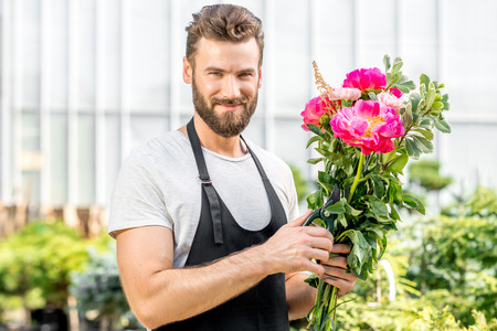 flower seller: Handsome flower seller making a beautiful bouquet with pink peonies in the flower shop Stock Photo