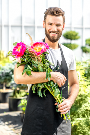 flower seller: Portrait of a handsome flower seller holding a beautiful bouquet with pink peonies in the shop