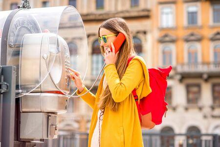 cabina telefonica: Mujer joven en el suéter amarillo y una mochila que llama con el teléfono público de la ciudad en la antigua ciudad italiana.