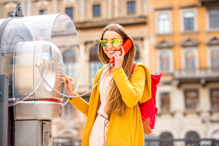 antique booth: Young woman in yellow sweater and backpack calling with city call box in the old italian town.