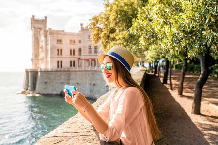 Young woman having fun photographing landscape near Miramare castle in northeastern Italy. Traveling in Italy