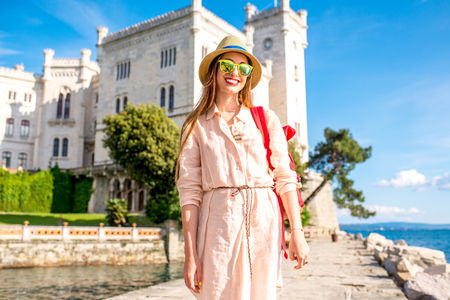 Jonge vrouwelijke reiziger lopen op de pier in de buurt van Miramare kasteel in het noordoosten van Italië Stockfoto - 61616756