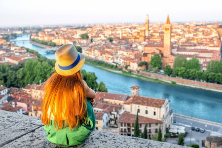 Woman enjoying beautiful view on Verona city in Italy on the sunrise. Verona is famous city of love in the north of Italy. Stock Photo