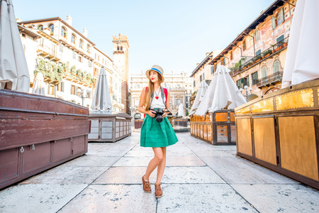 central market: Young female tourist standing on the central market square in Verona town.