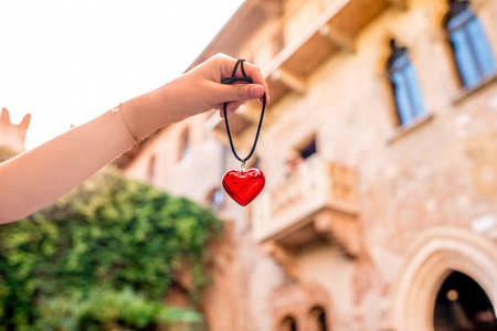 romeo: Holding a decoration in form of heart with Romeo and Juliet balcony on the background in Verona city