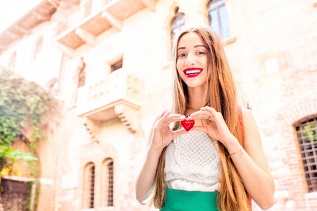 juliet: Beautiful woman holding decoration in the form of heart near Romeo and Juliet balcony in Verona. Romeo and Juliet is a romantic tragedy written by William Shakespeare