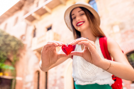 romeo juliet: Beautiful woman holding decoration in the form of heart near Romeo and Juliet balcony in Verona. Romeo and Juliet is a romantic tragedy written by William Shakespeare