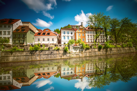 View on Ljubljanica river with old building in Ljubljana city in Slovenia. Long exposure image technic with blurred clouds and reflection on the water