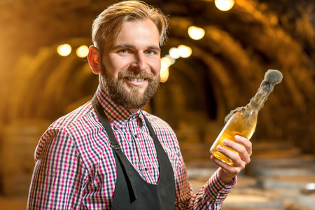 black mold: Sommelier holding old bottle of white wine with famous black mold in a wine cellar in Hungary Stock Photo
