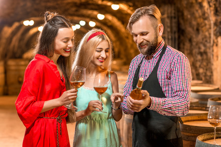Wine degustation with sommelier or wine maker and two pretty women in colorful dresses in the old cellar. Stock Photo