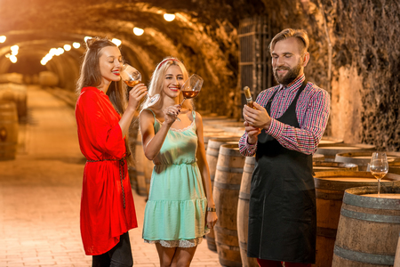 advise: Wine degustation with sommelier or wine maker and two pretty women in colorful dresses in the old cellar. Stock Photo