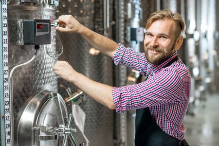 Handsome wine maker in working apron pouring wine to the glass at the wine manufacture with metal tanks for wine fermentation. Wine production at the modern factory Stock Photo