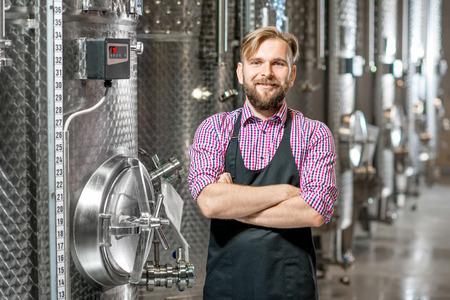 Portrait d'un beau fabricant de vins au tablier de travail à la fabrication avec des réservoirs métalliques pour la fermentation du vin. Production de vin à l'usine moderne Banque d'images - 61619288