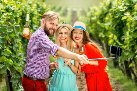 Tre amici con cappelli e bicchieri di vino divertirsi facendo foto selfie con lo smartphone e selfie bastone sulla vigna