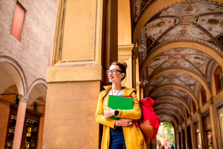 casually: Young female student dressed casually standing with books in the famous arched galleries in Bologna city in Italy. Bologna is a student city and home to the oldest university in the world