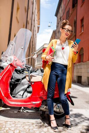 ouside: Young female student with books and backpack using smartphone standing near red scooter on the street in Bologna city in Italy Stock Photo