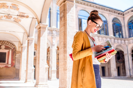 Young female student dressed casually with colorful books in the inner yard of oldest university in the world in Bologna city in Italy