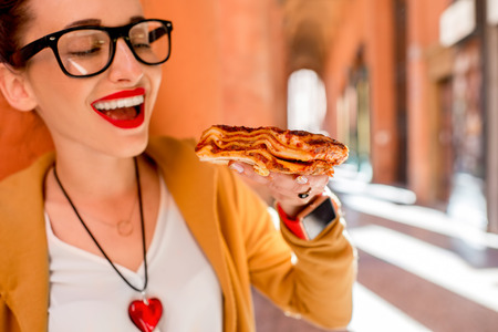 invented: Young woman eating lasagna with bolognese outdoors on the street in Bologna city in Italy. Lasagna bolognese was invented in Bologna city. Soft focus with small depth of field Stock Photo