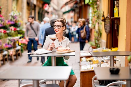 adult sandwich: Young woman sitting at the cafe with shakerato coffee and panini outdoor on the famous street with local food markets in Bologna city. Stock Photo