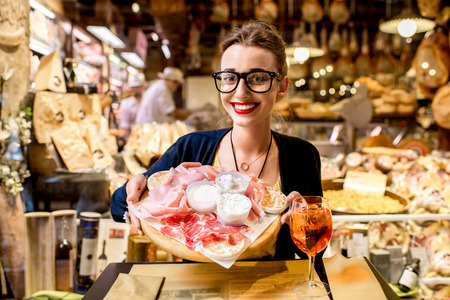 Young woman sitting near the food shop with traditional italian appetizer on the blurred food showcase background in Bologna city. Bologna is the gastronomic center of Italy Stock Photo