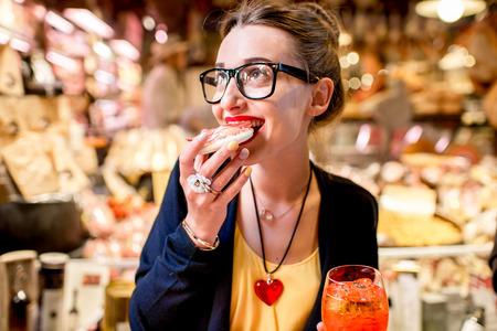 comiendo pan: Mujer joven que come el pan con jamón delante del escaparate de comida en la ciudad de Bolonia.