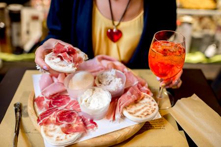 jamones: aperitivo italiano tradicional con proscioutto, salchicha de mortadela, queso, pan y bebida Aperol Spritz en la tabla de madera.