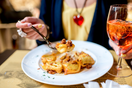 Eating a dish with traditional ring-shaped pasta tortellini and spritz aperol drink