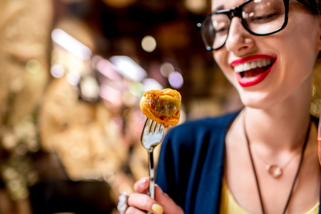 invented: Young woman eating tortellini pasta in front of the food shop in Bologna. Tortellini ring-shaped pasta was invented in Bologna.