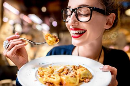 Junge Frau isst Tortellini Pasta vor dem Lebensmittelgeschäft in Bologna. Tortellini ringförmige Teigwaren wurden in Bologna erfunden.