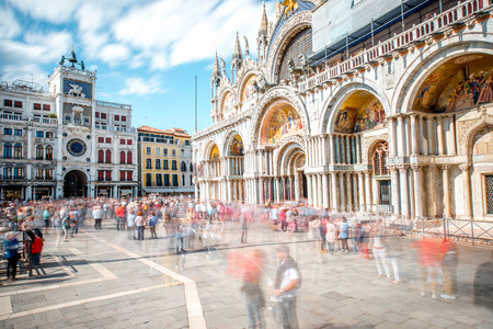 saint marks square: Saint Marks square with basilica and clocktower in Venice. Long exposure image technic with motion blurred people Stock Photo