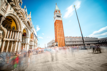 procuratie: Saint Marks square with campanille and basilica in Venice. Long exposure image technic with motion blurred people